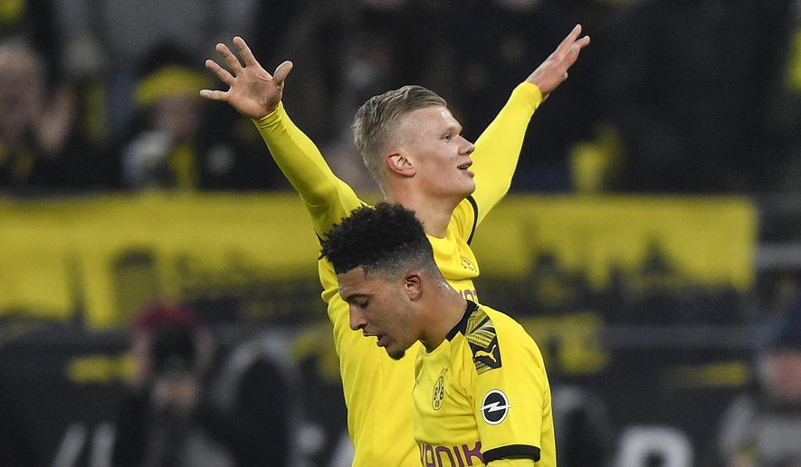 Dortmund's Erling Haaland, up, celebrates after scoring his side's 4th goal behind Dortmund's third scorer Jadon Sancho, during the German Bundesliga soccer match between Borussia Dortmund and 1. FC Cologne in Dortmund, Germany, Friday, Jan. 24, 2020. (AP Photo/Martin Meissner)