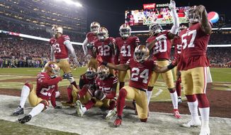 San Francisco 49ers players celebrate after cornerback Richard Sherman, bottom center, intercepted a pass against the Green Bay Packers during the second half of the NFL NFC Championship football game Sunday, Jan. 19, 2020, in Santa Clara, Calif. The 49ers won 37-20 to advance to Super Bowl 54 against the Kansas City Chiefs. (AP Photo/Tony Avelar)