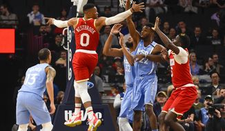 Houston Rockets guard Russell Westbrook(0) passes behind his back to center Clint Capela, right, as Minnesota Timberwolves center Karl-Anthony Towns(32), forward Andrew Wiggins(22) and guard Shabazz Napier(13) look onduring the first half of an NBA basketball game Friday, Jan. 24, 2020, in Minneapolis. (AP Photo/Craig Lassig)
