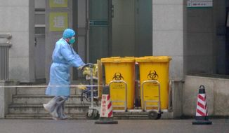 In this Wednesday, Jan. 22, 2020, file photo, a staff member moves bio-waste containers past the entrance of the Wuhan Medical Treatment Center in Wuhan, China, where some people infected with a new virus are being treated. The new virus comes from a large family of coronaviruses, some causing nothing worse than a cold. Others named SARS and MERS have killed hundreds in separate outbreaks. (AP Photo/Dake Kang, File) **FILE**