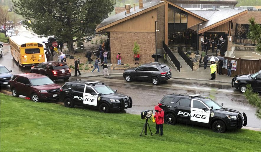 FILE - In this May 7, 2019, file photo, police and others are seen outside a recreation center where students are reunited with their parents after a shooting at STEM School Highlands Ranch, in the Denver suburb of Highlands Ranch, Colo. The security guard who accidentally injured two students while shooting at a deputy whom he thought was a shooter will not be criminally charged, but he must complete community service and attend a diversion program for improper use of a weapon on school grounds, a special prosecutor said Friday, Jan. 24, 2020. (AP Photo/David Zalubowski, File)