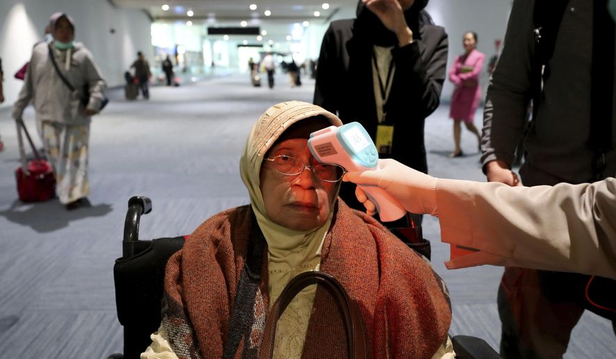 In this Wednesday, Jan. 22, 2020, file photo, a health official scans the body temperature of a passenger as she arrives at the Soekarno-Hatta International Airport in Tangerang, Indonesia. Indonesia is screening travelers from overseas for a new type of coronavirus as fears spread about a mysterious infectious disease after its first death reported in China. (AP Photo/Tatan Syuflana, File)