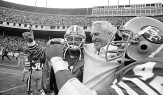 FILE - In this Nov. 29, 1981 file photo, San Francisco 49ers coach Bill Walsh is hugged by 49ers back Walt Easley, left, and 49ers back Ronnie Lott after beating the New York Giants 17-10 to clinch the division title at Candlestick Park in San Francisco. What doach Kyle Shanahan, quarterback Jimmy Garoppolo, defensive end Nick Bosa and the rest of the San Francisco 49ers are doing this year harkens back to 1981 when Bill Walsh, Joe Montana and Ronnie Lott led the franchise to its first Super Bowl title. (AP Photo/Carl Viti)