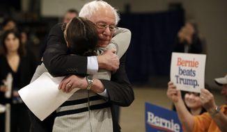 Democratic presidential candidate Sen. Bernie Sanders, I-Vt., center, hugs Rep. Alexandria Ocasio-Cortez, D-N.Y., after Sanders walked up to the podium to speak during a campaign event Saturday, Jan. 25, 2020, in Marshalltown, Iowa. (AP Photo/Marcio Jose Sanchez)