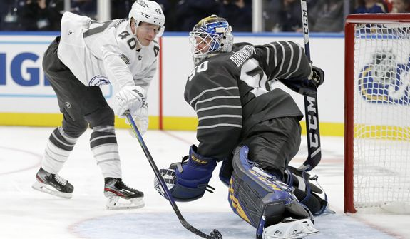 Vancouver Canucks forward Elias Pettersson (40) reaches for the puck as he closes in on St. Louis Blues goalie Jordan Binnington (50) in an NHL hockey All Star semifinal game Saturday, Jan. 25, 2020, in St. Louis. (AP Photo/Jeff Roberson) ** FILE **