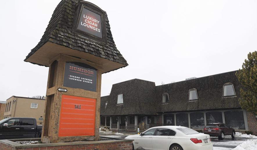 A car is parked by the sign of a Humidor cigar lounge in Lisle, Ill., on Saturday, Jan. 25, 2020.  A woman fatally shot a retired Illinois State Police trooper and wounded another retired state trooper and an off-duty trooper before turning the gun on herself at the cigar lounge Friday night, in the Chicago suburbs, police said.  (Abel Uribe/Chicago Tribune via AP)