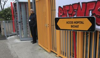 A man stands in the entrance door of the Bichat hospital in Paris, Saturday Jan. 25, 2020. France has announced three confirmed cases of the deadly new virus from China, the first cases in Europe and the first outside Asia and the United States. One of people who caught the virus is hospitalized in the southwestern city of Bordeaux. The others are in Paris. (AP Photo/Michel Euler)