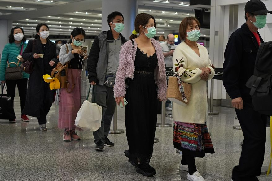 Passengers wear masks as they walk at the Hong Kong International Airport in Hong Kong Saturday, Jan. 25, 2020. Hong Kong has declared the outbreak of a new virus an emergency and will close primary and secondary schools for two more weeks after the Lunar New Year holiday. City leader Carrie Lam also announced Saturday that trains and flights from the city of Wuhan would be blocked. (AP Photo/Vincent Yu)