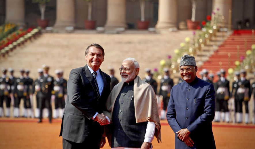 Brazil's President Jair Bolsonaro, left, shakes hand with Indian Prime Minister Narendra Modi, with Indian President Ram Nath Kovind standing beside them during his ceremonial welcome at the presidential palace in New Delhi, India, Saturday, Jan. 25, 2020. Bolsonaro is this year's chief guest for India's Republic day parade. (AP Photo/Manish Swarup)