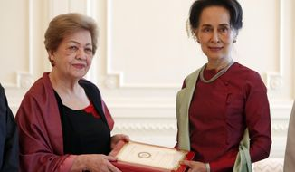FILE - In this Jan. 20, 2020, file photo, Myanmar's leader Aung San Suu Kyi, right, receives a final report from Philippine diplomat Rosario Manalo, a member of the Independent Commission of Enquiry for Rakhine State, at the Presidential Palace in Naypyitaw, Myanmar. When Suu Kyi walked into the International Court of Justice in December, 2019, she gambled the remaining shreds of her hard-won international reputation on a rebuttal of accusations that her country's military committed genocide against minority Rohingya Muslims. (AP Photo/Aung Shine Oo, File)