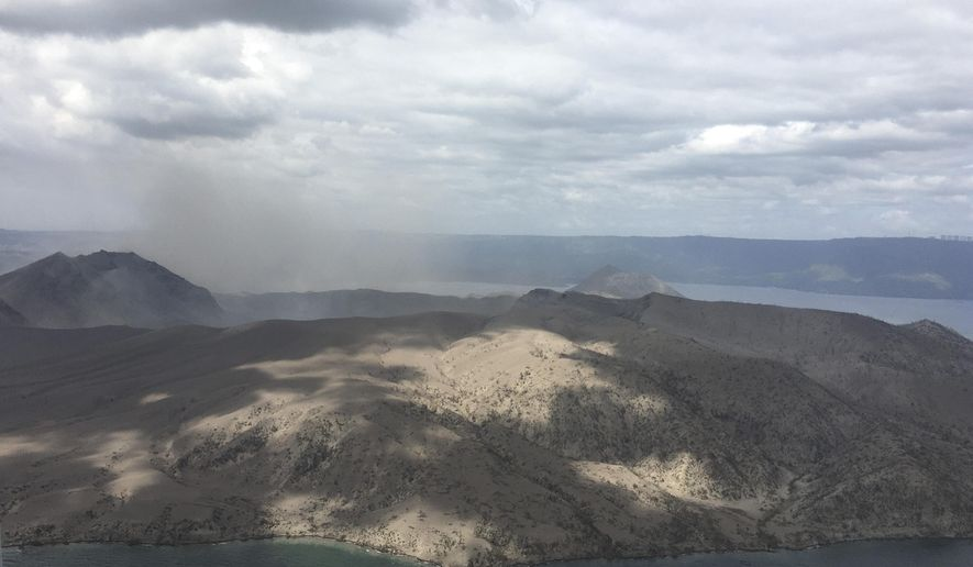 In this Jan. 21, 2020, handout photo provided by the Office of Civil Defense, Taal volcano emits small amounts of ash in Batangas province, southern Philippines. The government will no longer allow people to live on the crater-studded island that's home to the volcano. (Office of Civil Defense via AP)