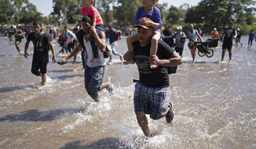 Central American migrants carry children as they run across the Suchiate River from Guatemala to Mexico, near Ciudad Hidalgo, Mexico, Monday, Jan. 20, 2020. More than a thousand Central American migrants hoping to reach the United States marooned in Guatemala are walking en masse across a river leading to Mexico in an attempt to convince authorities there to allow them passage through the country. (AP Photo/Santiago Billy)