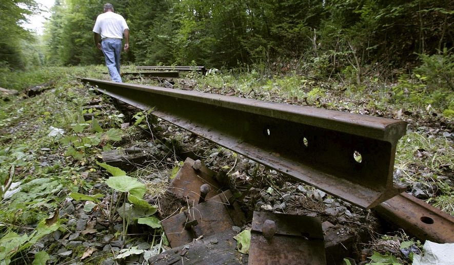 FILE - In this Aug. 23, 2005, file photo, Don Glover, Caledonia County Coordinator for the Vermont Association of Snow Travelers, walks past rails and ties being removed from an old railbed in Danville, Vt. Completion of a 93-mile rail trail across northern Vermont got a big boost when Republican Gov. Phil Scott requested funds in the 2020 budget to complete the project. (AP Photo/Alden Pellett, File)