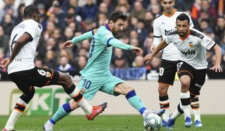 Barcelona's Lionel Messi, center, tries to dribble past Valencia's Geoffrey Kondogbia, left, and Valencia's Francis Coquelin during the Spanish La Liga soccer match between Valencia and Barcelona at the Mestalla Stadium in Valencia, Spain, Saturday, Jan. 25, 2020. (AP Photo/Alberto Saiz)