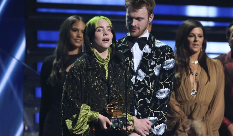 """Billie Eilish, left, and Finneas O'Connell accept the award for song of the year for """"Bad Guy"""" at the 62nd annual Grammy Awards on Sunday, Jan. 26, 2020, in Los Angeles. At right looking on is presenter Karen Fairchild. (Photo by Matt Sayles/Invision/AP)"""