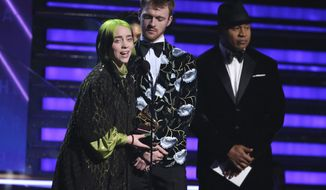 """Billie Eilish, left, and Finneas O'Connell accept the award for album of the year for """"When We All Fall Asleep, Where Do We Go?"""" at the 62nd annual Grammy Awards on Sunday, Jan. 26, 2020, in Los Angeles. Looking on at right is presenter LL Cool J. (Photo by Matt Sayles/Invision/AP)"""