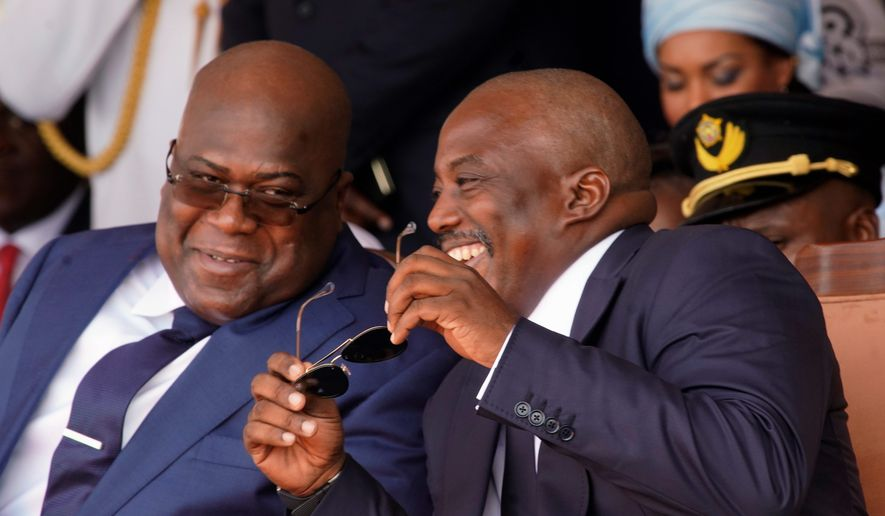 Congolese President Felix Tshisekedi, left, and outgoing president Joseph Kabila share a light moment side during the inauguration ceremony in Kinshasa, Democratic Republic of the Congo, Thursday Jan. 24, 2019. Tshisekedi won an election that raised numerous concerns about voting irregularities amongst observers as the country chose a successor to longtime President Kabila. (AP Photo/Jerome Delay)