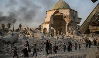 """Civilians fled as Iraqi forces advanced on Mosul in 2017 after oppressive occupation by the Islamic State. Shifa al-Nima, a Muslim religious scholar, said he """"issued fatwas to confiscate houses of displaced people and permitted ISIS fighters to blow up mosques."""" (Associated Press)"""