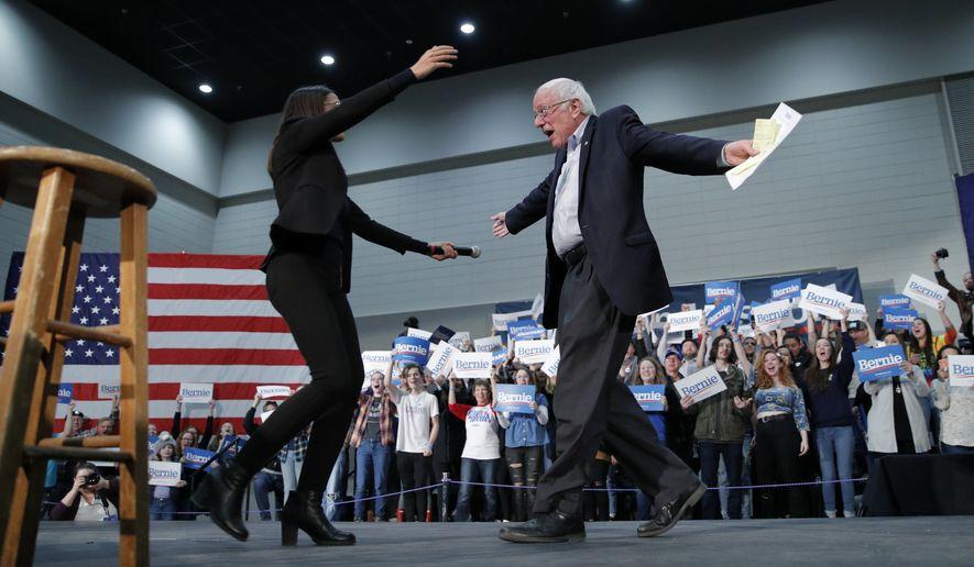 Democratic presidential candidate Sen. Bernie Sanders, I-Vt., right, embraces Rep. Alexandria Ocasio-Cortez, D-NY, at a campaign rally Sunday, Jan. 26, 2020, in Sioux City, Iowa. (AP Photo/John Locher)