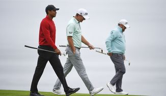 Tiger Woods, left, walks with Tom Hoge and J.B. Holmes on the fourth hole of the South Course at Torrey Pines Golf Course during the final round of the Farmers Insurance golf tournament Sunday, Jan. 26, 2020, in San Diego. (AP Photo/Denis Poroy)