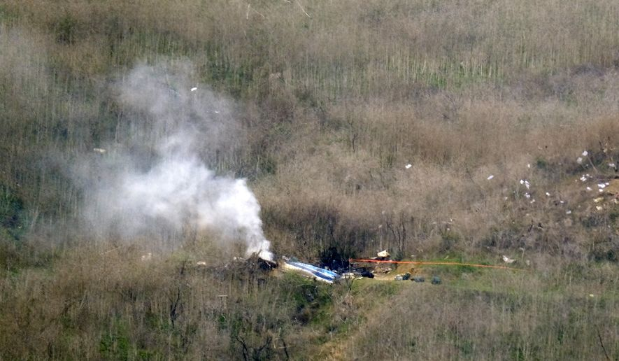 Smoke rises from the charred remains of a helicopter on the side of a hill in Calabasas, Calif. where NBA All-Star Kobe Bryant was killed on Sunday Jan. 26, 2020. (AP Photo/Richard Vogel)