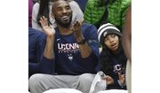 Kobe Bryant and his daughter Gianna watch the first half of an NCAA college basketball game between Connecticut and Houston in Storrs, Conn. (AP Photo/Jessica Hill)