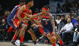 Washington Wizards guard Bradley Beal (3) drives tot he basket against Atlanta Hawks center Damian Jones (30) during the first half of an NBA basketball game on Sunday, Jan. 26, 2020, in Atlanta. (AP Photo/Todd Kirkland)
