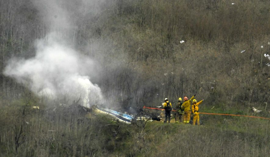 Firefighters work the scene of a helicopter crash where former NBA star Kobe Bryant died, Sunday, Jan. 26, 2020, in Calabasas, Calif. (AP Photo/Mark J. Terrill)