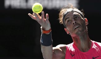 Spain's Rafael Nadal serves to compatriot Pablo Carreno Busta during their third round singles match at the Australian Open tennis championship in Melbourne, Australia, Saturday, Jan. 25, 2020. (AP Photo/Dita Alangkara)