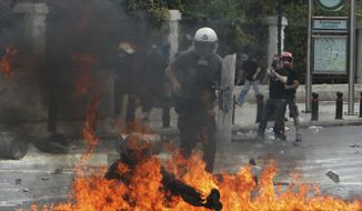 FILE - In this Wednesday, May 5, 2010, file photo, a riot police officer is engulfed in flames from a fire bomb thrown by protesters in central Athens, during a protest against harsh new spending cuts aimed at saving their country from bankruptcy. The debt crisis in Europe and particularly in Greece raised serious questions in Britain about developments in the European Union even though Britain did not use the euro currency, contributing to the Brexit vote in June 2016. Britain is scheduled to leave the EU on Jan. 31, 2020 after 47 years of membership. (AP Photo/Thanassis Stavrakis, File)