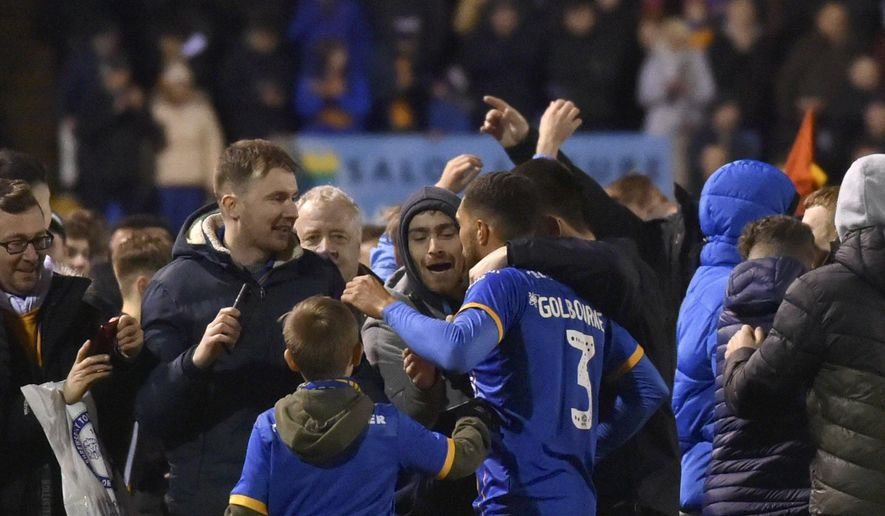 Shrewsbury's Scott Goldbourne, center, celebrates with fans at the end of the English FA Cup fourth round soccer match between Shrewsbury Town and Liverpool at the Montgomery Waters Meadow in Shrewsbury, England, Sunday, Jan. 26, 2020. (AP Photo/Rui Vieira)