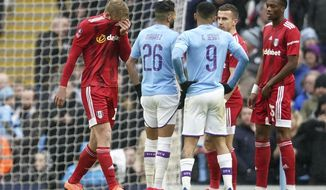 Fulham's Tim Ream, left, reacts after being shown a red card for a foul in the box during an English FA Cup fourth round soccer match between Manchester City and Fulham at the Etihad Stadium in Manchester, England, Sunday, Jan. 26, 2020. (AP Photo/Jon Super)