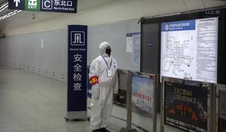 A worker wearing a hazardous materials suit stands at the entrance to a subway station in Beijing, Sunday, Jan. 26, 2020. The new virus accelerated its spread in China, and the U.S. Consulate in the epicenter of the outbreak, the central city of Wuhan, announced Sunday it will evacuate its personnel and some private citizens aboard a charter flight. (AP Photo/Mark Schiefelbein)
