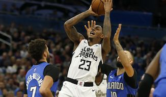 Los Angeles Clippers guard Lou Williams (23) shoots between Orlando Magic guards Evan Fournier (10) and Michael Carter-Williams (7) during the second quarter of an NBA basketball game in Orlando, Fla., Sunday, Jan. 26, 2020. (AP Photo/Reinhold Matay)