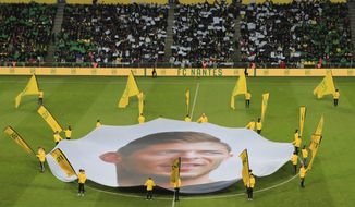 A giant canvas showing late Argentinian player Emiliano Sala is pictured in La Beaujoire stadium prior the French League One soccer match between Nantes against Bordeaux in Nantes, western France, Sunday, Jan. 26, 2020. Nantes paid an emotional tribute to Emiliano Sala by wearing a special blue and white (AP Photo/Michel Euler)
