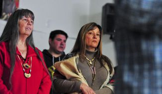 Colleen Hill, left, council secretary and treasure of the Little Shell Chippewa Tribe, and Laurelyn Baker stand for the beginning of of the pipe ceremony to honor the tribe's federal recognition, Saturday, Jan. 25, 2020 at the Shawn Gilbert Event Center in Great Falls, Mont. (Rion Sanders/Great Falls Tribune via AP