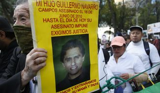 """A demonstrator carries a poster with the photo of his murdered son during a march against violence called """"Walk for Peace,"""" in Mexico City, Sunday, Jan. 26, 2020. Thousands marched making their way towards Mexico City's main square the Zocalo. The text on the poster reads in Spanish """"Mi son Guillermo Navarro Campos. Murdered on June 16, 2010. His murder is still unpunished to this day. We demand justice. We love you and miss you. Mom and Dad."""" (AP Photo/Ginnette Riquelme)"""