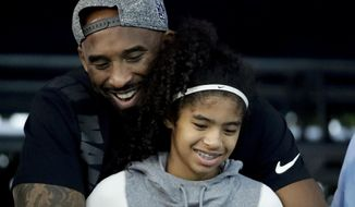 In this July 26, 2018 file photo former Los Angeles Laker Kobe Bryant and his daughter Gianna watch during the U.S. national championships swimming meet in Irvine, Calif. Bryant, the 18-time NBA All-Star who won five championships and became one of the greatest basketball players of his generation during a 20-year career with the Los Angeles Lakers, died in a helicopter crash Sunday, Jan. 26, 2020. Gianna also died in the crash. She was 13. (AP Photo/Chris Carlson)