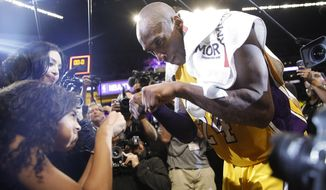 FILE - In this April 13, 2016 file photo Los Angeles Lakers' Kobe Bryant, right, fist-bumps his daughter Gianna after the last NBA basketball game of his career, against the Utah Jazz in Los Angeles. Bryant, the 18-time NBA All-Star who won five championships and became one of the greatest basketball players of his generation during a 20-year career with the Los Angeles Lakers, died in a helicopter crash Sunday, Jan. 26, 2020. Gianna also died in the crash. (AP Photo/Jae C. Hong, file)