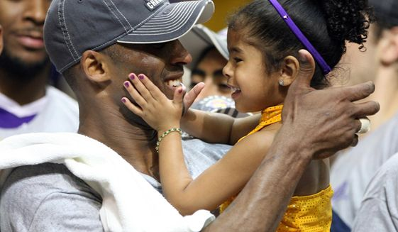 In this June 14, 2009, photo, Los Angles Lakers guard Kobe Bryant celebrates with his daughter Gianna, following the Lakers 99-86 defeat of the Orlando Magic in Game 5 of the NBA Finals at Amway Arena in Orlando. (Stephen M. Dowell/Orlando Sentinel via AP) ** FILE **