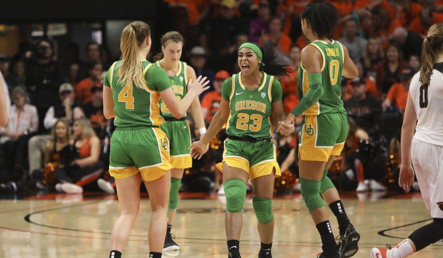 Oregon's Minyon Moore (23) celebrates with Jaz Shelley (4), Sabrina Ionescu (20) and Satou Sabally (0) following Oregon's victory over Oregon State in an NCAA college basketball game in Corvallis, Ore., Sunday, Jan. 26, 2020. (AP Photo/Amanda Loman)  **FILE**