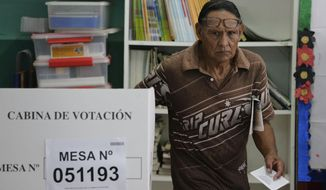 A man leaves a voting booth after voting in the congressional elections at a public school at the Villa El Salvador shantytown of Lima, Peru, Sunday, Jan. 26, 2020. Peruvians are voting to elect 130 new members of the congress that will legislate for only one year, in place of the congress that was dissolved by president Martin Vizacarra in September 2019. (AP Photo/Martin Mejia)