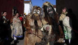 """In this photo taken on Monday, Jan. 20, 2020, people in traditional costumes take part in the traditional """"Las Carantonas"""" festival in Acehuche, Spain. The Carantonas involves men pulling on animal hides that make them look like Chewbacca. At the Carantoñas festival in Acehuche, men are helped to pull on hairy, bulky costumes and scary masks before they walk down streets of whitewashed houses looking like wild beasts (""""carantoñas""""). Women parade in colorful embroidered shawls and skirts as music plays. (AP Photo/Manu Fernandez)"""