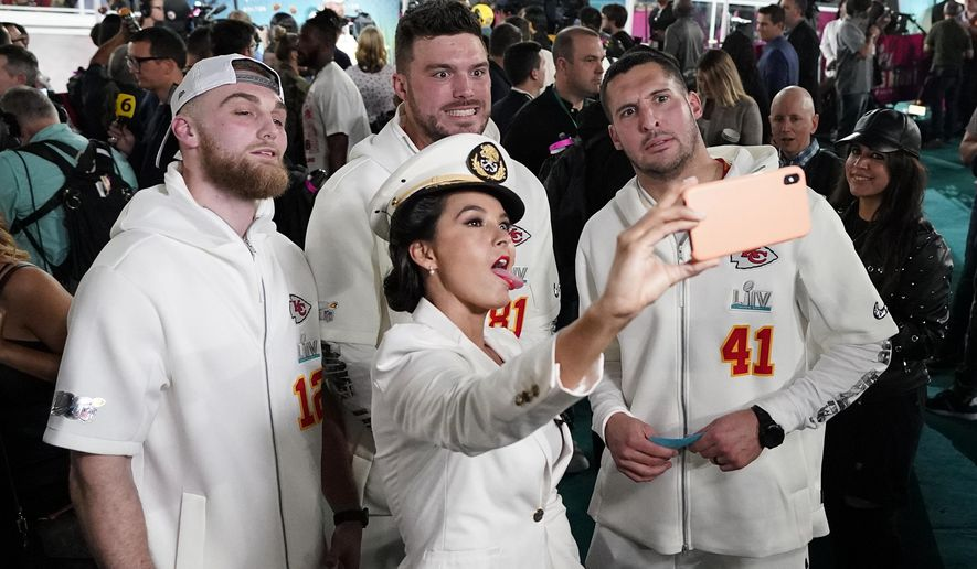 Gerdina Holguin, with TUDN television, poses with Kansas City Chiefs players during Opening Night for the NFL Super Bowl 54 football game Monday, Jan. 27, 2020, at Marlins Park in Miami. (AP Photo/David J. Phillip)