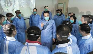 In this photo released by China's Xinhua News Agency, Chinese Premier Li Keqiang, center, speaks with medical workers at Wuhan Jinyintan Hospital in Wuhan in central China's Hubei province, Monday, Jan. 27, 2020. China on Monday expanded its sweeping efforts to contain a deadly virus, extending the Lunar New Year holiday to keep the public at home and avoid spreading infection. (Li Tao/Xinhua via AP)
