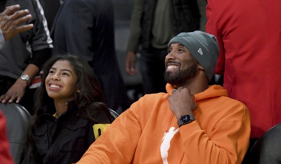 Former Los Angeles Laker Kobe Bryant and his daughter Gianna Bryant attend an NBA basketball game between the Los Angeles Lakers and Dallas Mavericks Sunday, Dec. 29, 2019, in Los Angeles. (AP Photo/Michael Owen Baker)
