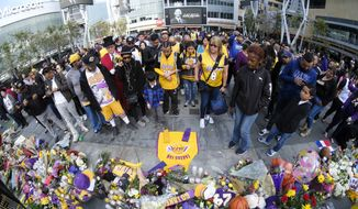People gather at a memorial for Kobe Bryant near Staples Center Monday, Jan. 27, 2020, in Los Angeles. Bryant, the 18-time NBA All-Star who won five championships and became one of the greatest basketball players of his generation during a 20-year career with the Los Angeles Lakers, died in a helicopter crash Sunday. (AP Photo/Ringo H.W. Chiu)