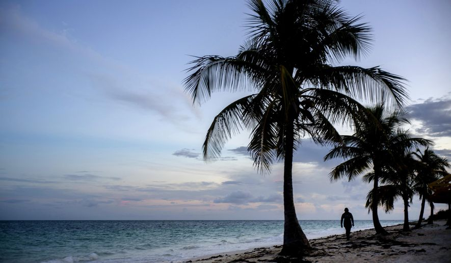 FILE - This Aug. 31, 2019 file photo shows a woman walking along a beach before the arrival of Hurricane Dorian in Freeport, Grand Bahama, Bahamas. Airbnb is giving five people a chance to spend a two-month sabbatical in the Bahamas in an attempt to boost the Caribbean island after it suffered damage from Hurricane Dorian last year. Contest winners will work with the Bahamas National Trust for two months on projects including coral reef restoration, pineapple farming and boat building.  (AP Photo/Ramon Espinosa, File)