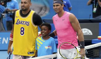 Australia's Nick Kyrgios, left, poses for a photo with Rafael Nadal, wearing a shirt as a tribute to Kobe Bryant ahead of his fourth round singles match at the Australian Open tennis championship in Melbourne, Australia, Monday, Jan. 27, 2020. (AP Photo/Lee Jin-man)