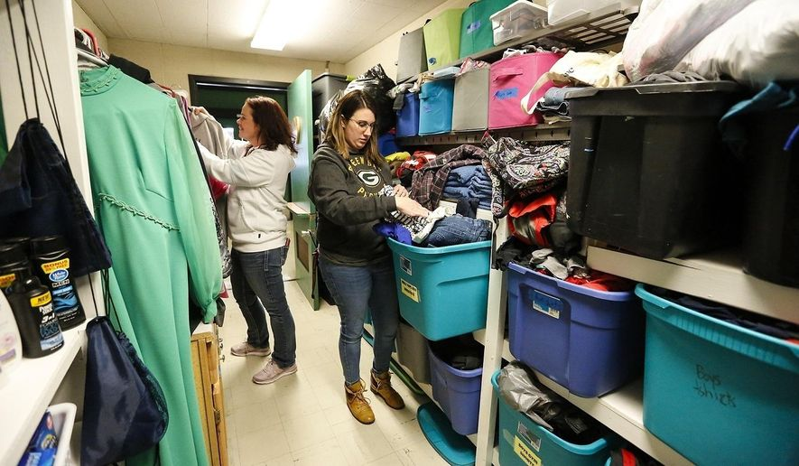 Woodworth Middle School teachers Gillian King and Nora Ballwanz arrange clothing items in the caring closet Friday, Jan. 17, 2020 at Woodworth Middle School in Fond du Lac, Wis. The caring closet provides clothing and hygiene items that some students may need. (Doug Raflik/The Reporter via AP)